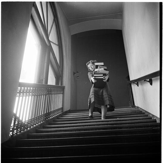 Image of girl carrying a big stack of books, while walking down stairs