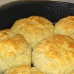 An image of old fashioned homemade biscuits in a cast iron skillet